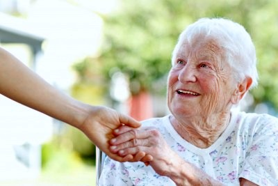 Elderly woman holding hand
